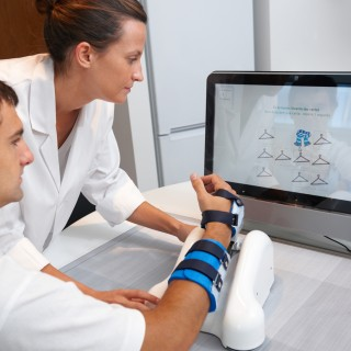 Investigator and patient with assistive robot for upper limb rehabilitation at home